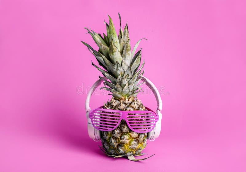 Trendig moderiktig ananasfrukt med hörlurar och solexponeringsglas lyssnar till musiken över ljus pastellfärgad rosa bakgrund arkivbilder