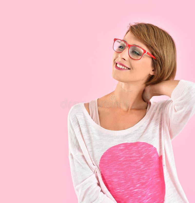 Trendig moderiktig flicka som bär rött glasögon arkivbild