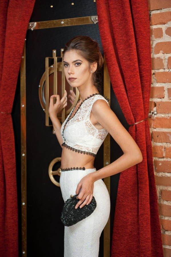 Trendig sinnlig attraktiv dam med det vita klänninganseendet nära ett kassaskåp i en tappningplats kvinna för brunetthårkortslutn arkivbild