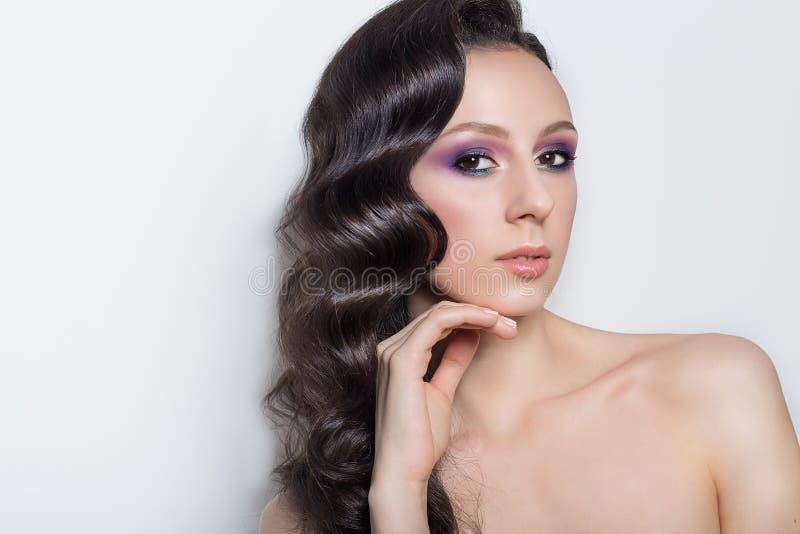Trendig stående av en härlig ung flicka med långt svart hår med den ljusa makeup- och aftonfrisyren i studion på en gr arkivfoton