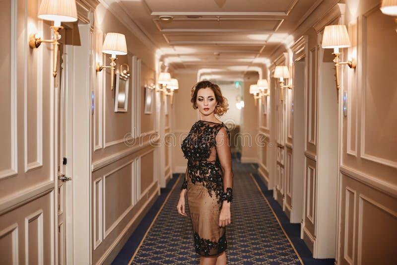 Trendig ung brunettkvinna med ljus makeup och med den perfekta sexiga kroppen i den stilfulla klänningen som poserar på tappningh royaltyfria foton