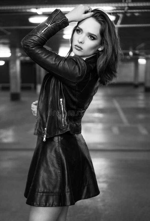 Trendig ung brunettkvinna som poserar bärande läderskir royaltyfria foton