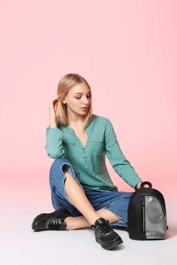 Trendig ung kvinna i stilfulla skor med ryggsäcken som sitter på bakgrund fotografering för bildbyråer