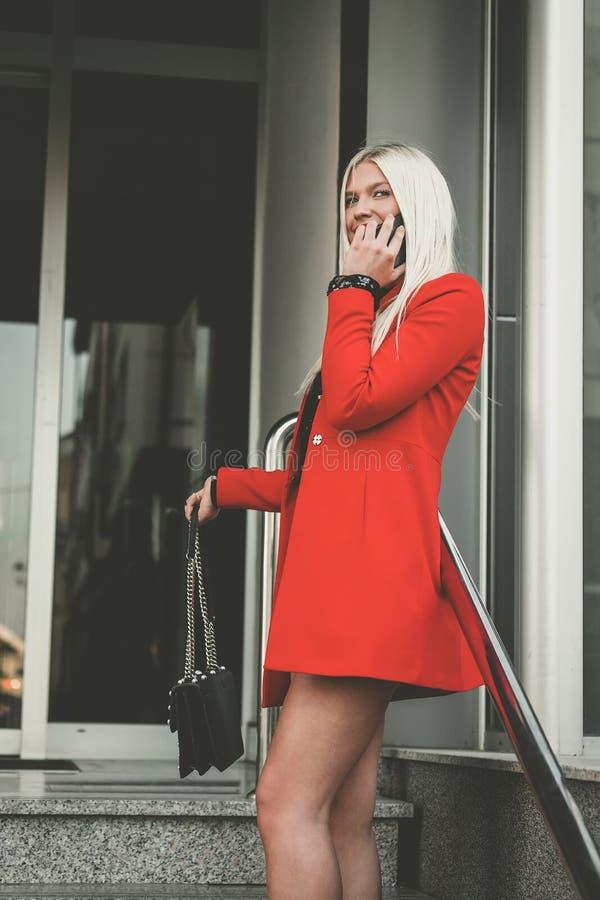 Trendig ung kvinna som talar på telefonen royaltyfri fotografi