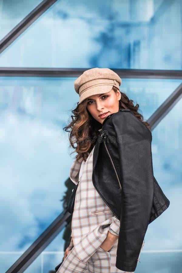 Trendig ung kvinna som utomhus poserar mot exponeringsglasf?nster royaltyfri fotografi