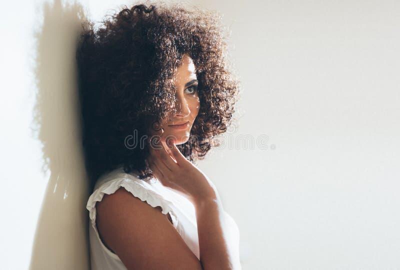 Trendig ung kvinnlig modell med det nätta leendet som poserar mot vit studioväggbakgrund Gullig flicka med arkivbilder