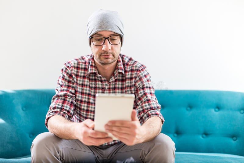 Trendig ung man som använder minnestavlaapparaten, medan sitta på hans kontor royaltyfria foton