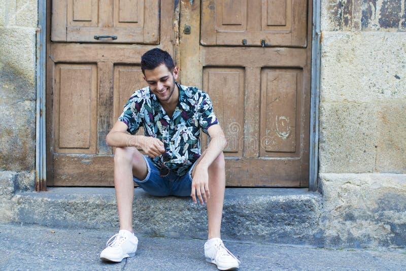 Trendig ung man som placeras i den gamla gatan royaltyfria foton