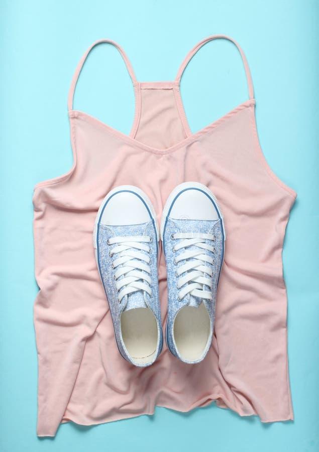 Trendiga gymnastikskor ligger på T-tröja på blå bakgrund, minimalism, bästa sikt royaltyfri foto