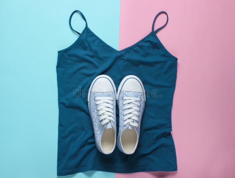 Trendiga gymnastikskor ligger på T-tröja på blå rosa pastellfärgad bakgrund, minimalism, bästa sikt royaltyfri foto
