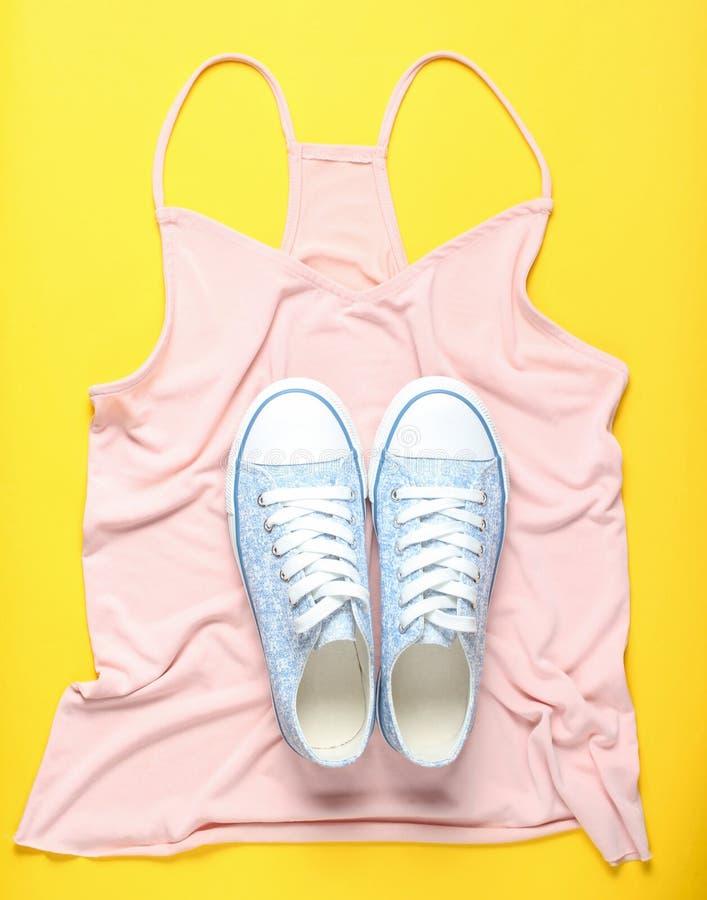 Trendiga gymnastikskor ligger på T-tröja på gul bakgrund, minimalism, bästa sikt arkivbilder