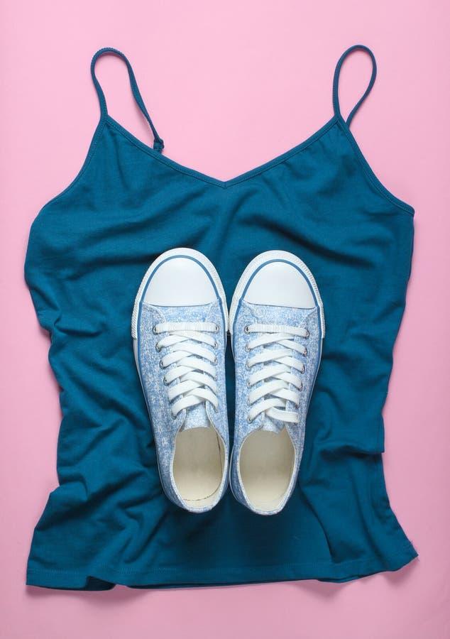 Trendiga gymnastikskor ligger på T-tröja på rosa bakgrund, minimalism, bästa sikt arkivbild