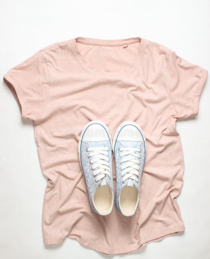Trendiga gymnastikskor ligger på T-tröja på vit bakgrund, minimalism, bästa sikt royaltyfri foto