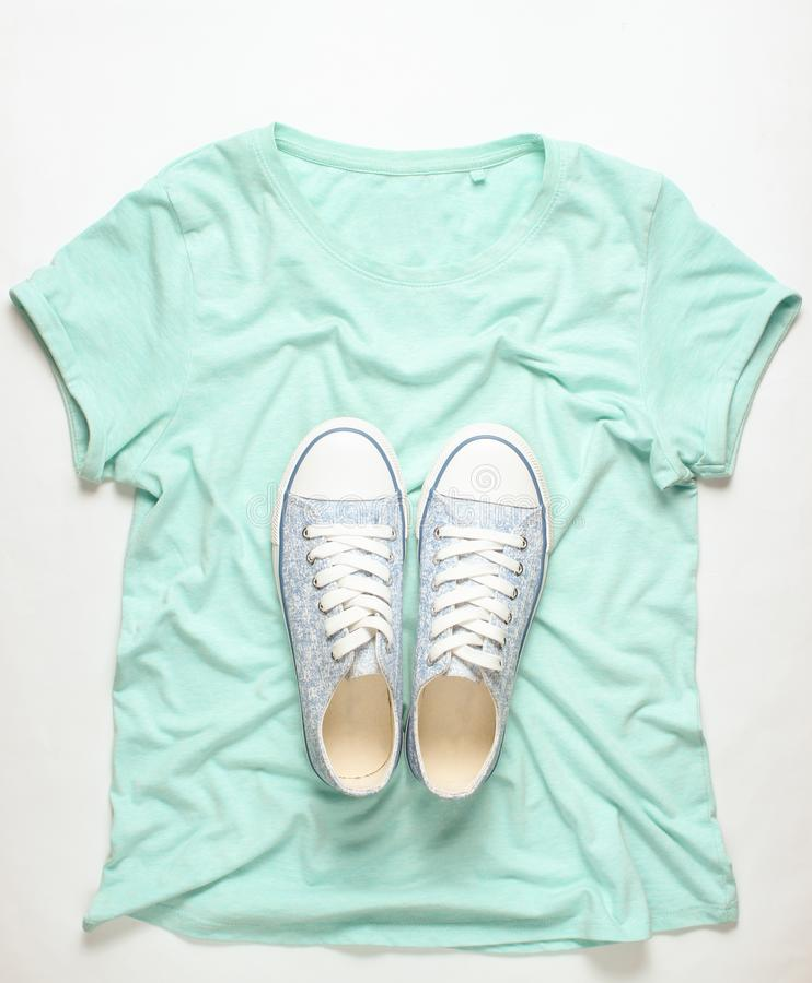 Trendiga gymnastikskor ligger på T-tröja på vit bakgrund, minimalism, bästa sikt royaltyfria foton