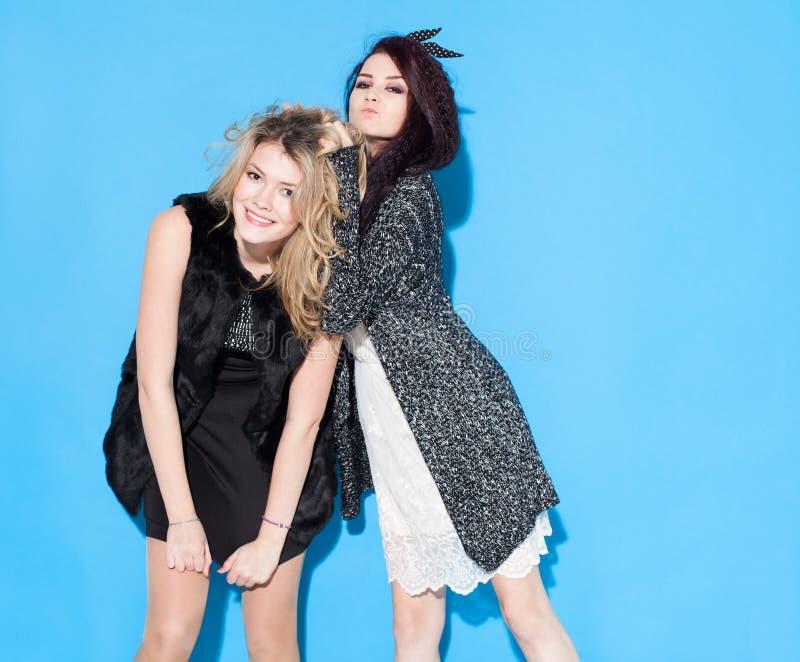 Trendiga härliga unga flickvänner som tillsammans står nära en blå bakgrund Brunetthår vrider blondinen Ha roligt och po royaltyfri foto