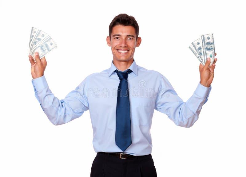 Trendiga hållande kontanta dolllars för ung man arkivfoto