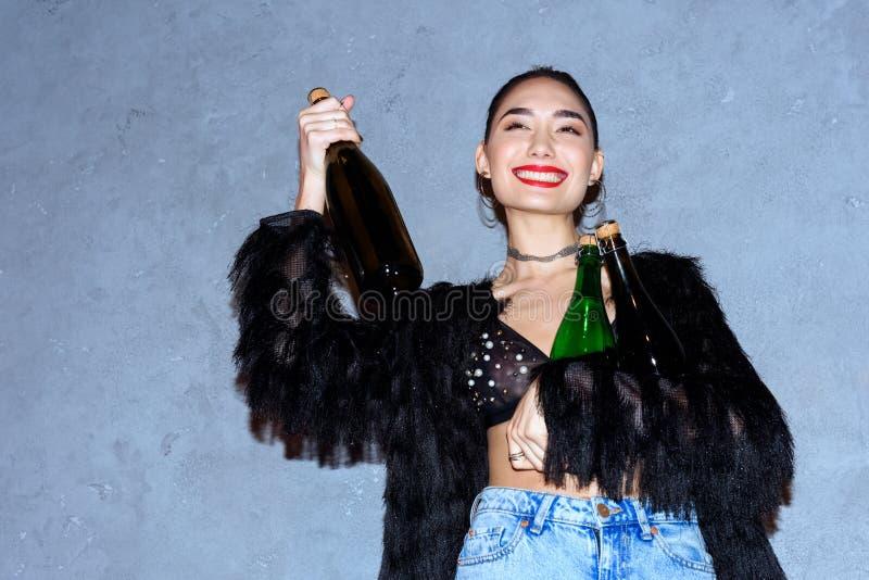 trendiga lyckliga asiatiska flickainnehavflaskor med alkoholdrycker arkivfoton