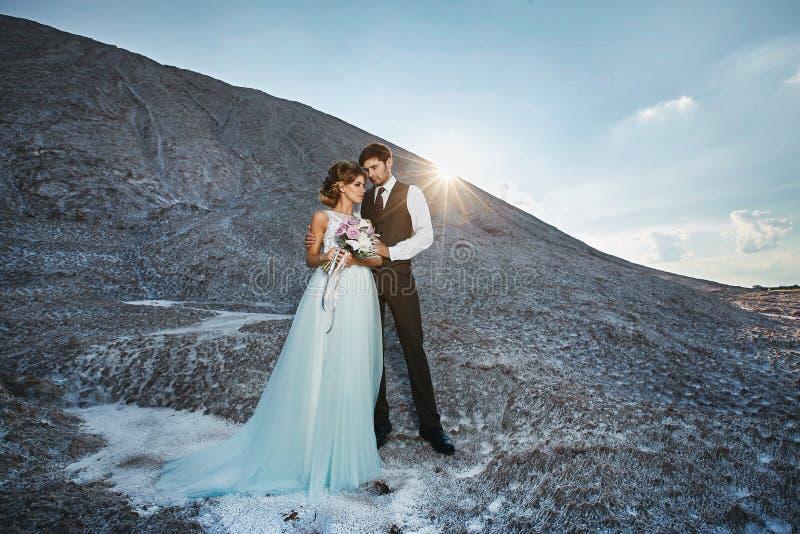Trendiga och härliga par, lycklig blond modellflicka med den stilfulla frisyren, i en vit snör åt klänningen och stilfullt royaltyfria foton