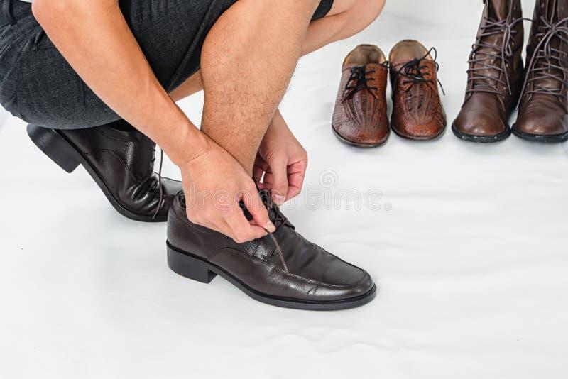 Trendiga skor för läder för man` s klassiska, man binder upp hans skosnöre på vit bakgrund arkivbild