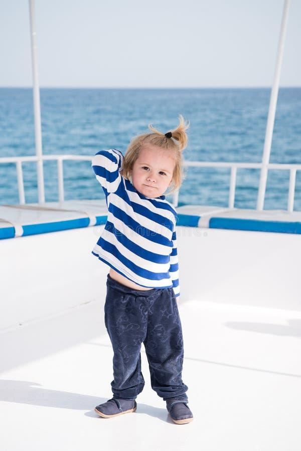 Trendiga små behandla som ett barn pojken på yachten i den marin- skjortan, flåsanden fotografering för bildbyråer