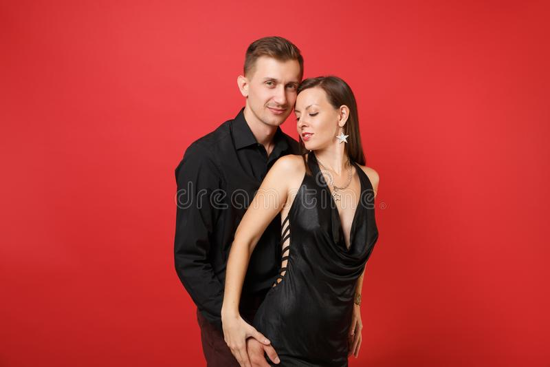 Trendiga unga par i den svarta kläderskjortaklänningen som firar födelsedagferiepartiet på ljust rött royaltyfri foto