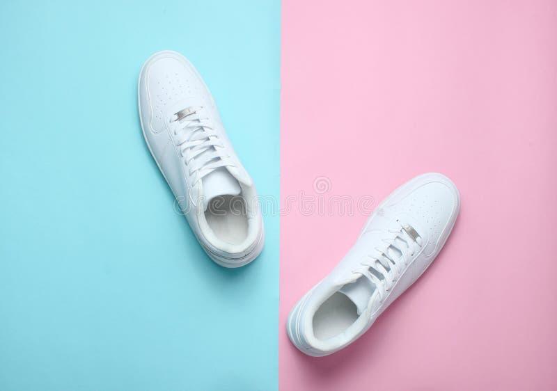 Trendiga vita gymnastikskor på en kulör pastellfärgad bakgrund, minimalism, bästa sikt, idérik orientering royaltyfri foto