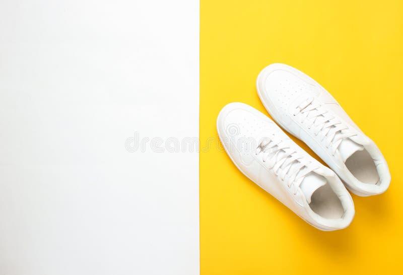 Trendiga vita gymnastikskor på en kulör pastellfärgad bakgrund, minimalism, bästa sikt, idérik orientering royaltyfria foton