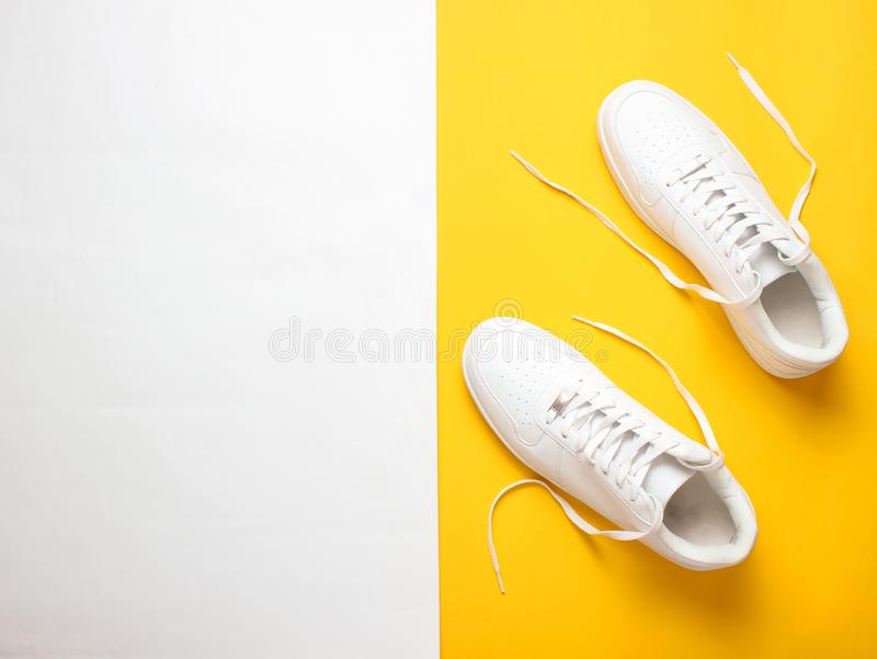 Trendiga vita gymnastikskor på en kulör pastellfärgad bakgrund, minimalism, bästa sikt, idérik orientering royaltyfria bilder