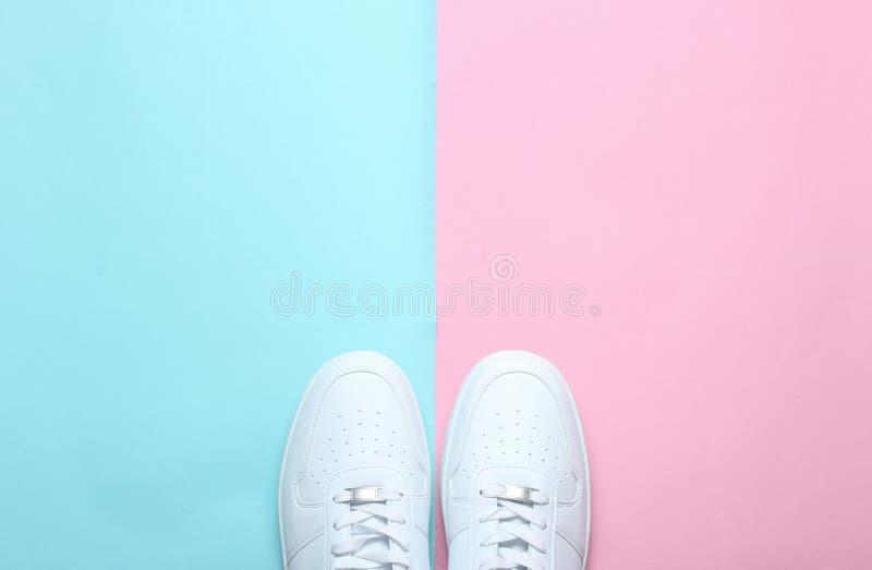 Trendiga vita gymnastikskor på en kulör pastellfärgad bakgrund, minimalism, bästa sikt, idérik orientering arkivfoto