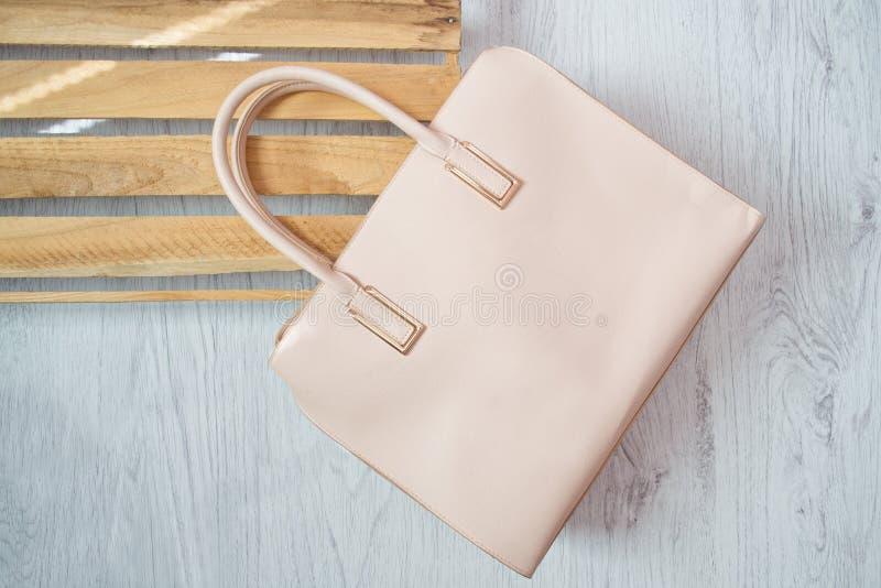 trendigt begrepp Beige handväska TWooden ask på backgrounen arkivfoton