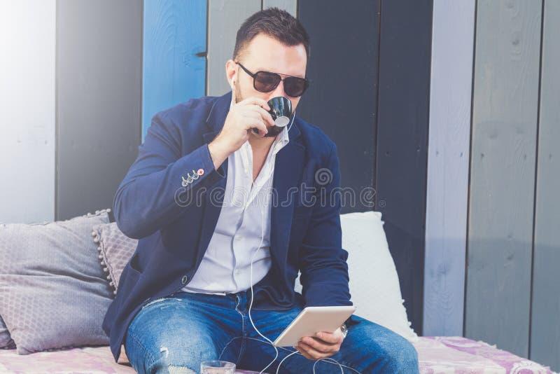 Trendigt sammanträde för ung man i digital minnestavlaapparat för coffee shop och för innehav royaltyfria bilder