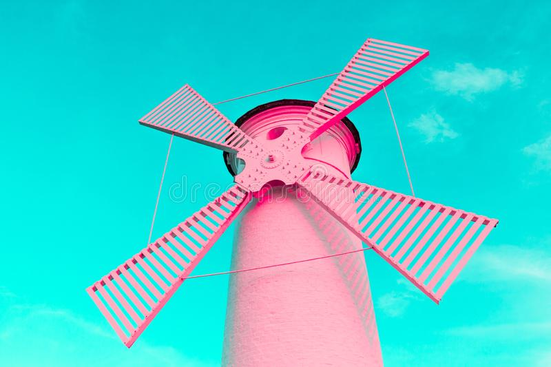 Trending color coral pink surreal lighthouse windmill on a blue pastel background royalty free stock image