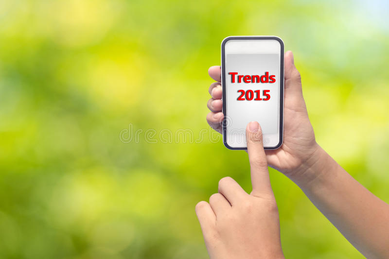 2015 Trends on Cell Phone Screen. Hand holding and finger pointing to a cell phone with the words Trends 2015 on the screen royalty free stock image