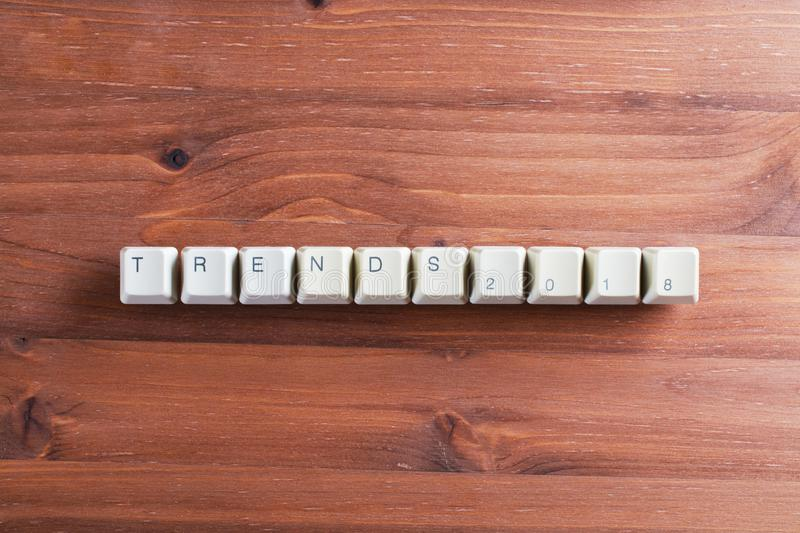 Trends 2018 concept on computer keyboard keys on a wooden background stock photography