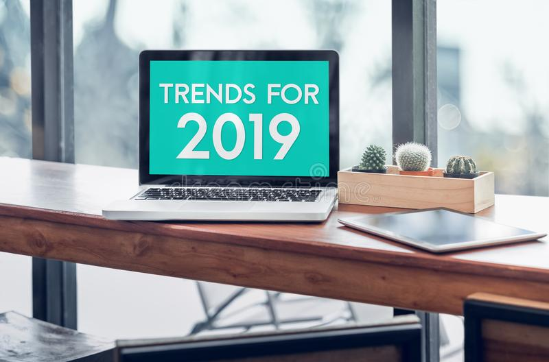 Trends for 2019 word in laptop computer screen with tablet on wood stood table in at window with blur background,Digital Business royalty free stock photo
