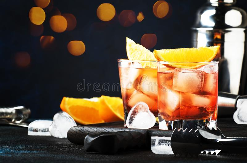 Trendy alcoholic cocktail Negroni with dry gin, red vermouth and red bitter, orange slice and ice cubes. Brown bar counter. Background, bar tools, night mood stock photos