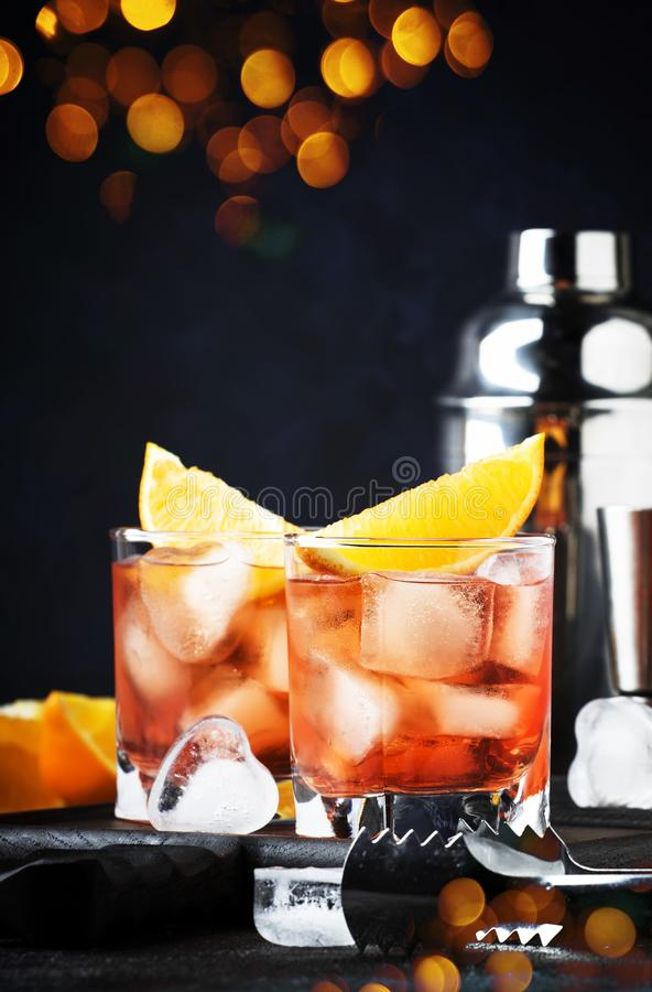 Trendy alcoholic cocktail Negroni with dry gin, red vermouth and red bitter, orange slice and ice cubes. Brown bar counter. Background, bar tools, night mood stock photography