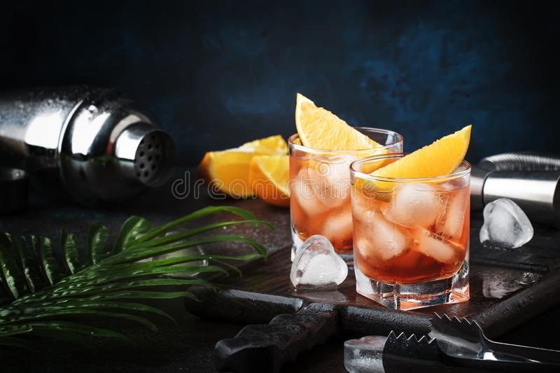 Trendy alcoholic cocktail Negroni with dry gin, red vermouth and red bitter, orange slice and ice cubes. Brown bar counter. Background, bar tools, night mood stock images