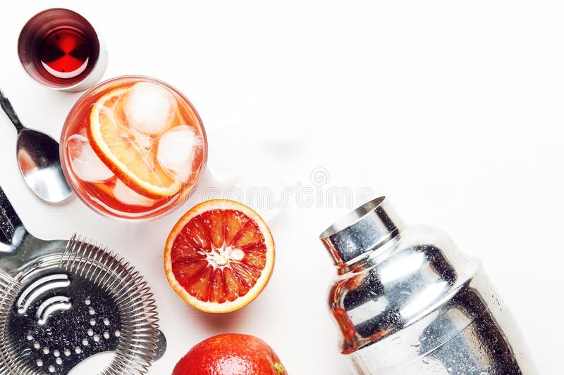 Trendy alcoholic cocktail Negroni with dry gin, red vermouth and red bitter, orange slice and ice cubes. White background, bar. Tools, top  view, copy space royalty free stock photos