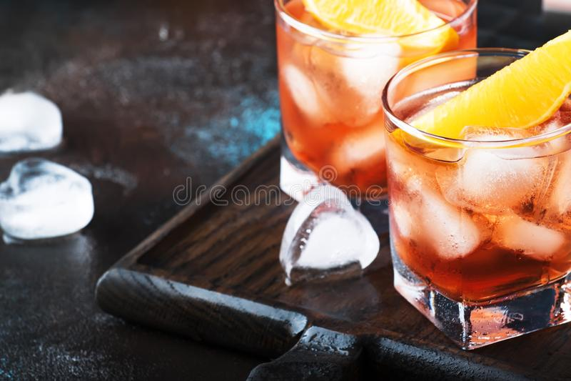 Trendy alcoholic cocktail Negroni with dry gin, red vermouth and red bitter, orange slice and ice cubes. Brown bar counter. Background, bar tools, night mood royalty free stock photography