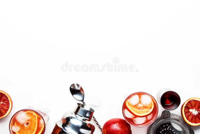 Trendy alcoholic cocktail Negroni with dry gin, red vermouth and red bitter, orange slice and ice cubes. White background, bar. Tools, top view, copy space stock images
