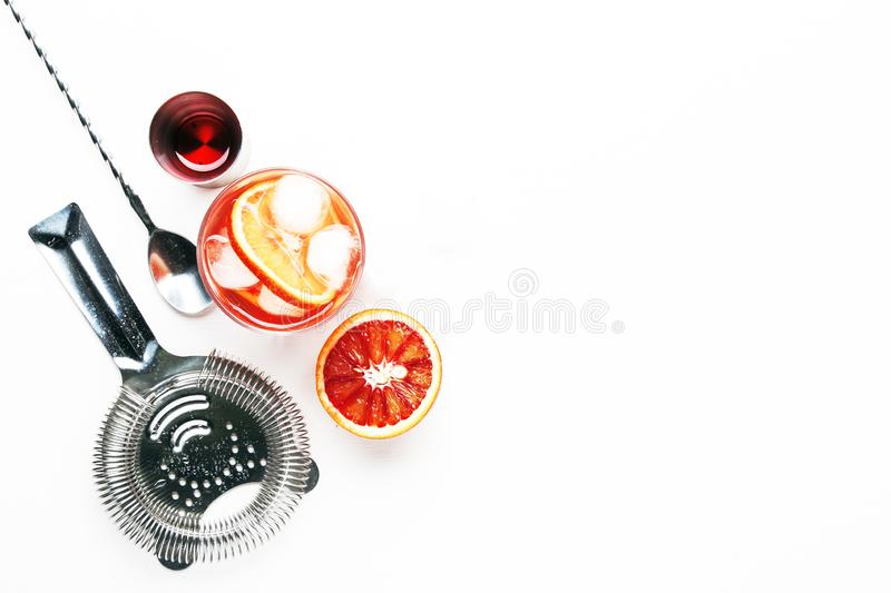 Trendy alcoholic cocktail Negroni with dry gin, red vermouth and red bitter, orange slice and ice cubes. White background, bar. Tools, top view, copy space royalty free stock photography