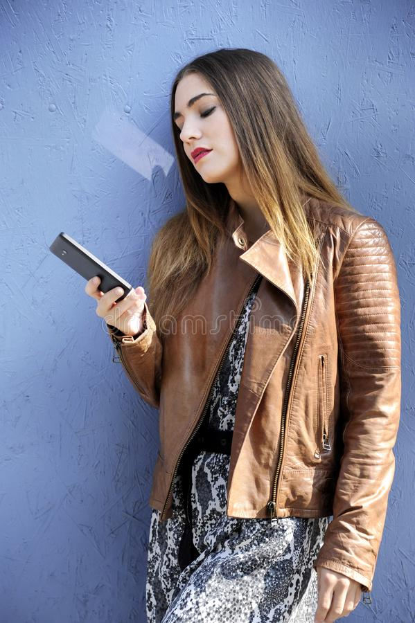 Trendy and attractive hipster woman is watching her mobile`s screen in front of a blue wall background. royalty free stock photo