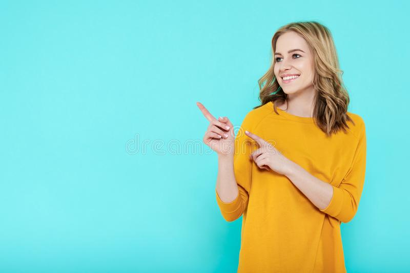 Trendy attractive young woman wearing casual clothes posing over pastel blue background. Smiling woman pointing with both hands. stock image