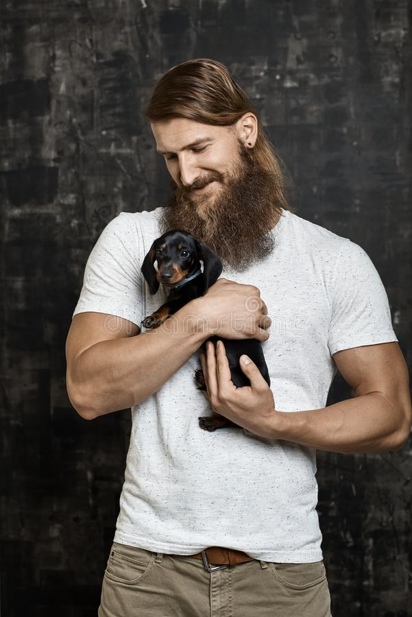 Muscular bearded man holding little dog stock photo