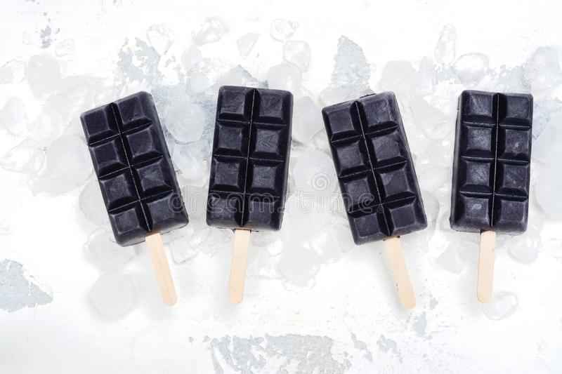 Trendy black charcoal ice cream popsicles royalty free stock image