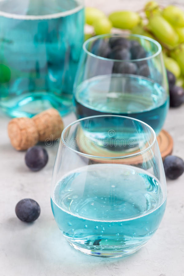 Trendy blue moscato wine in glass and in bottle, green and red grape on background, vertical stock images