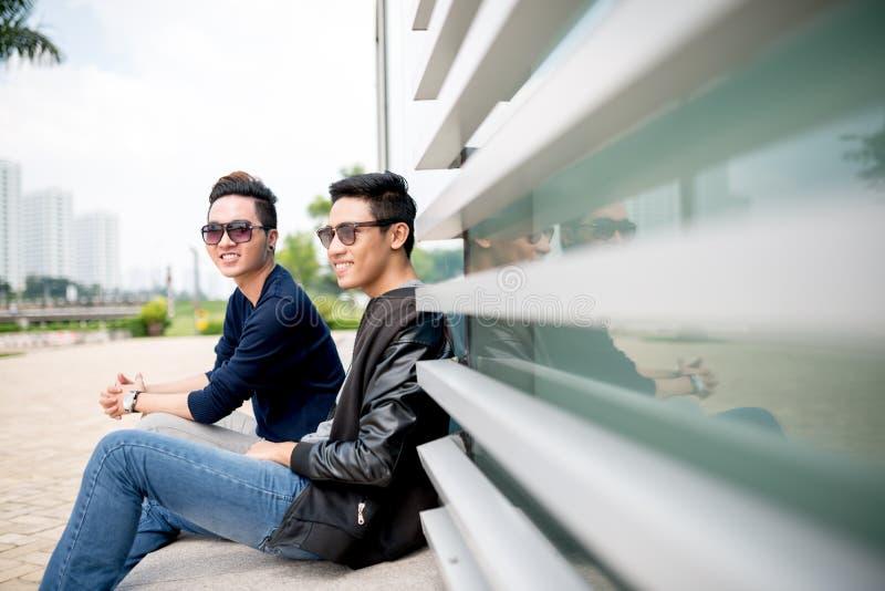 Trendy boys. Smiling trendy boys sitting outdoors royalty free stock image