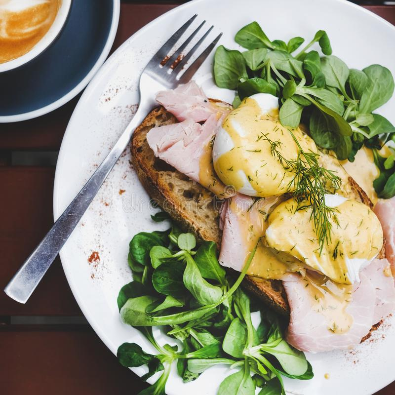 Breakfast with poached eggs on bread with ham, square crop. Trendy breakfast set. Flat-lay of poached Eggs Benedict on sourdough bread toast with green salad and stock photos