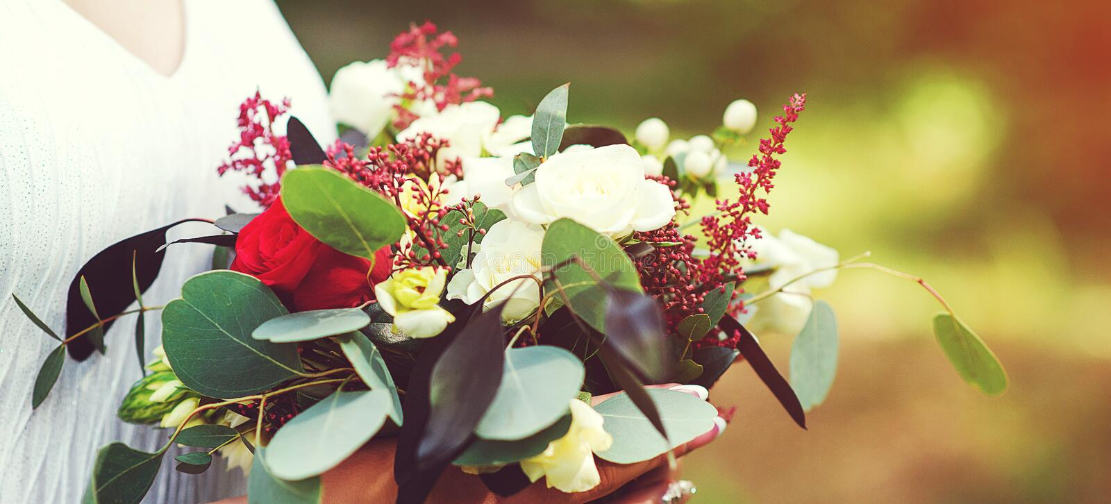 Trendy bridal bouquet.Beautiful bouquet of red flowers. Beautiful flowers in girl hands. Fashion wedding bouquet. Wedding. Decorations. Copy space. Wedding stock images